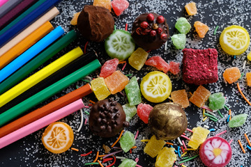 Sweets and pencils on sugarly background
