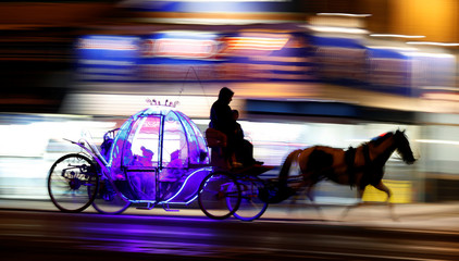 Children travel on an illuminated horse drawn carriage as they pass under the illuminations on the promenade in Blackpool, northern England
