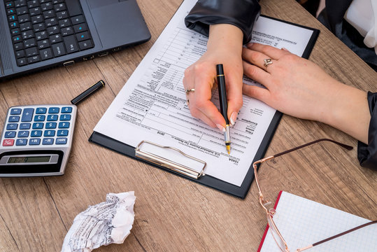 Woman filing individual income tax form 1040, with calculator. close up.