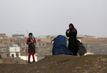 A family stand on a hilltop overlooking Kabul