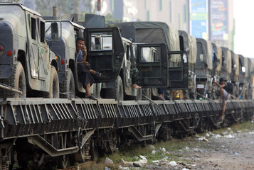 A soldier uses his mobile phone aboard a train carrying military vehicles and supplies in Khon Kaen province
