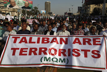 Supporters of Pakistan's MQM political party hold a banner as they listen to speeches from their leaders during a rally to show their solidarity to Pakistan's armed forces in Karachi