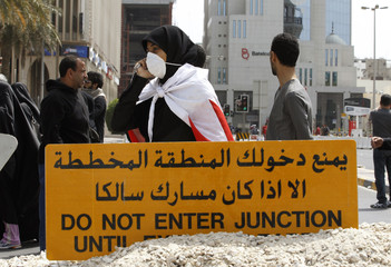Anti-government protesters use a sign from a nearby construction site to block the roads from riot police at the junction of Bahrain Financial Harbour in Manama