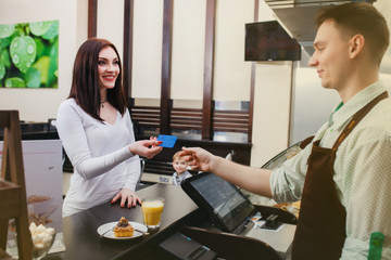 Young beautiful woman buys cake and juice in cafe with card