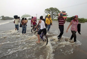 People wade through a flooded section of the Pan-American Highway in Chinandega city