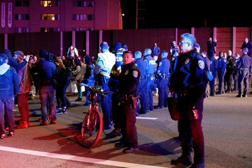 Police keep watch as demonstrators protest against President-elect Donald Trump in Minneapolis
