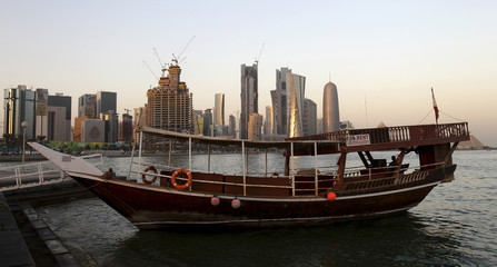A traditional wooden fishing Dhow is seen during sunset in a port near buildings along the Doha skyline