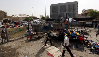 Men walk past the site of a suicide bomb attack in Baghdad