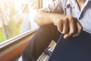 young man is sitting reading in the window in the room with soft-focus in the background. over light and vintage colors tone