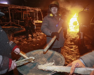 Pro-European protesters bang on a metal barrel during a rally in Kiev