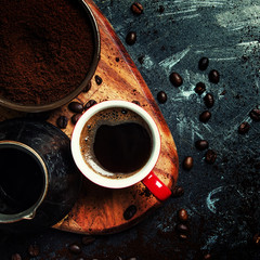 Ground coffee, Turkish coffee maker, cup with hot espresso, dark background, top view