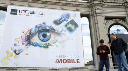 People walk by the Mobile World Congress main entrance in Barcelona