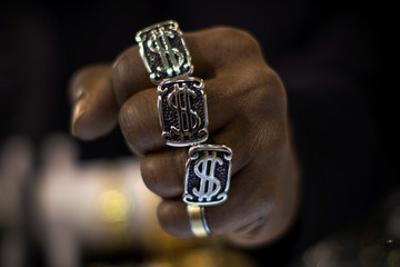 A man wears dollar sign rings in a jewellery shop in Manhattan in New York City