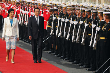Thailand's Prime Minister Yingluck Shinawatra and China's Premier Li Keqiang inspect honor guard at the government house in Bangkok