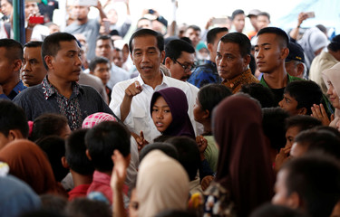 Indonesian President Joko Widodo speaks to residents outside a collapsed mosque following this week's earthquake in Pidie Jaya,