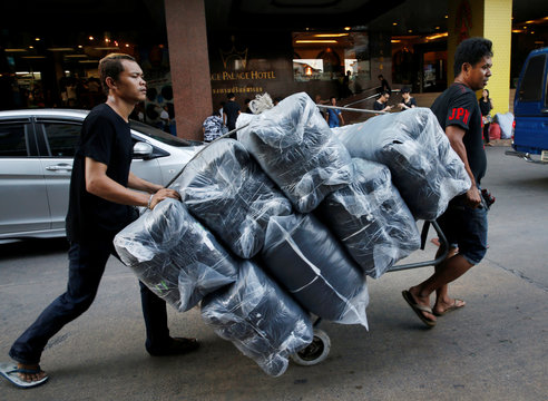 People restock black T-shirts for shoppers mourning the passing of Thai King Bhumibol Adulyadej at Bo Bae wholesale market in Bangkok