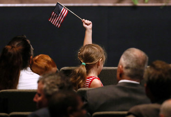 A young girl waves an American flag during a memorial service for three slain Baton Rouge police officers at Healing Place Church in Baton Roug