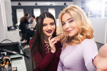 Two beautiful girlfriends are sitting and making selfie in a beauty salon