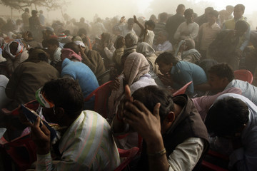 People cover themselves from the rising dust caused by the helicopter of Rahul Gandhi as he arrives for an election campaign rally at Meja town