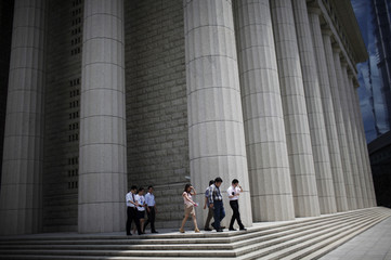 Workers leave an office building during lunch break at the financial district of Shanghai