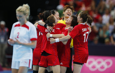 South Korea's players celebrate after defeating Denmark in their women's handball Preliminaries Group B match at the Copper Box venue during the London 2012 Olympic Games