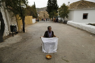 Jose Garcia asks for alms during the Christ of Pano pilgrimage in Moclin, southern Spain