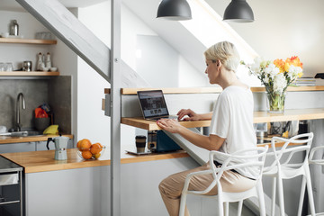 Back view of a woman sitting at kitchen and using her laptop.