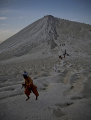 Hindu devotees pay homage while racing from the crater of the Chandargup mud volcano to others nearby in Pakistan's Balochistan province
