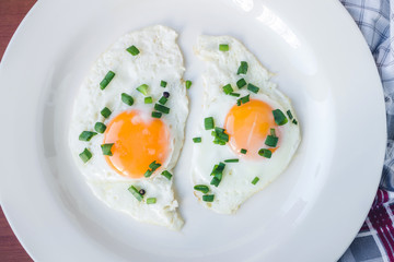 Fried eggs in white plate on napkin, close-up, top view
