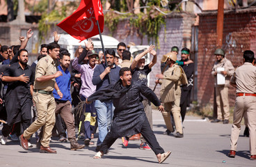 A Kashmiri Shi'ite Muslim mourner flagellates himself as they are stopped by Indian policemen while trying to participate in a Muharram procession during a curfew in downtown Srinagar