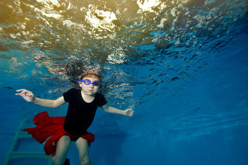 Beautiful little girl swims and dances underwater in the red skirt against the yellow lights and looks at me. Portrait. Shooting under water. Landscape orientation