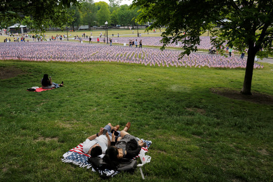 A couple lies on blanket with a U.S. flag pattern next to a field of United States flags displayed by the Massachusetts Military Heroes Fund on the Boston Common in Boston,