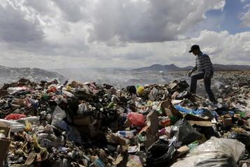 Bolivian student Esteban Quispe walks on a rubbish dump in Patacamaya, south of La Paz
