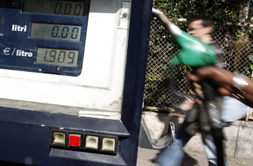 An attendant prepares to refuel a car at a petrol station in downtown Rome
