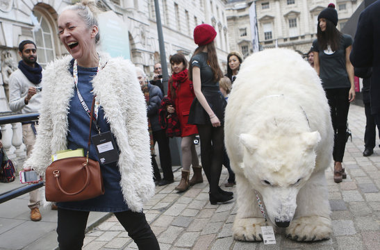 Beauty writer Anna-Marie Solowij laughs after spotting a Greenpeace activist dressed as a polar bear as they walk past Somerset House for London Fashion Week