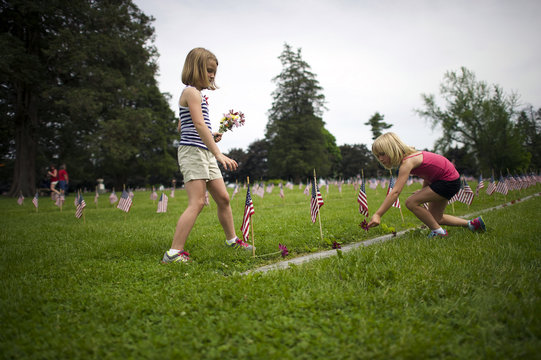 Sisters Rachel and Brooke Masenheimer place flowers on the grave sites of Battle of Gettysburg soldiers during a ceremony at National Soldier's Cemetery following the Gettysburg Memorial Day parade in Gettysburg, Pennsylvania, May 26, 2014.