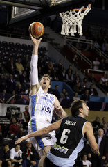Argentina's Nocioni scores over Uruguay's Aguiar during their first round match of the FIBA Americas Championship in Mar del Plata