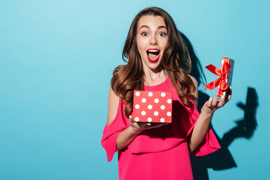 Excited cute girl in dress holding opened present box