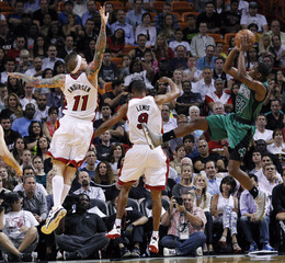 Miami Heat's Chris Andersen defends with teammate Rashard Lewis as Boston Celtics' Jordan Crawford shoots in the first half of their NBA basketball game in Miami, Florida
