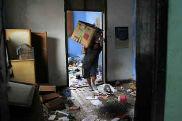 """A man carries his belongings at his home in a traditional building known as """"Casona El Buque"""", following a fire, in Barrios Altos"""