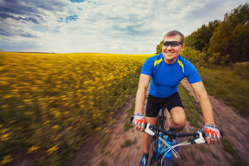 A male cyclist is riding on a picturesque yellow rapeseed field.