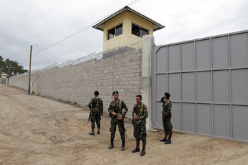 Soldiers stand guard outside a new prison in El Porvenir