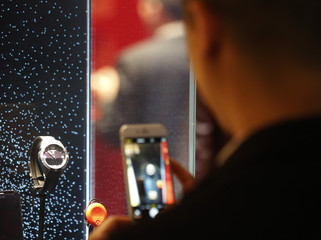 A visitor takes a picture of a Tissot smartwatch at the Baselworld watch and jewellery fair in Basel