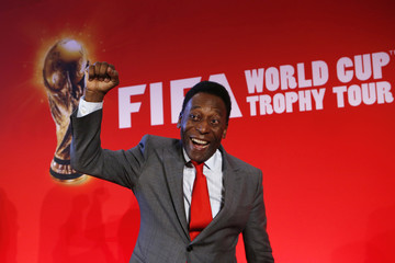 """Brazilian soccer legend Pele reacts as he poses after a news conference to present the FiFA World Cup global """"Trophy Tour"""" in Paris"""