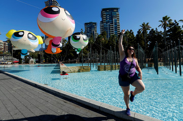 A women poses for her friend to take a picture with Powerpuff Girls balloons, outside at the pop culture event Comic-Con International in San Diego