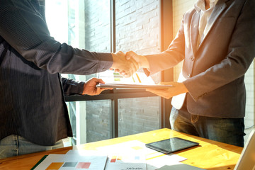 Businessmen shake hands when entering into business deal,In the hand are document files.