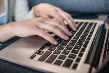 Cropped shot of human hands typing on keyboard of laptop