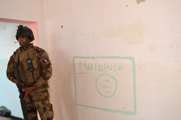 A member of the Iraqi security forces stands next to a drawing on a wall of a flag used by Islamic State militants, south of Falluja
