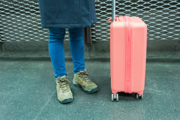 Teenage traveler is standing with pink suitcase luggage