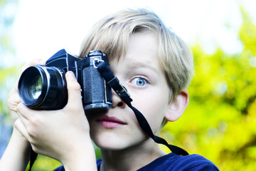 Little child blond boy with an old camera shooting outdoor. Kid taking a photo using a vintage retro film camera. Summer nature background
